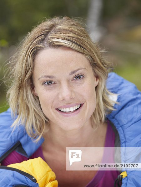 Woman with sleeping bag wrapped around her smiling.