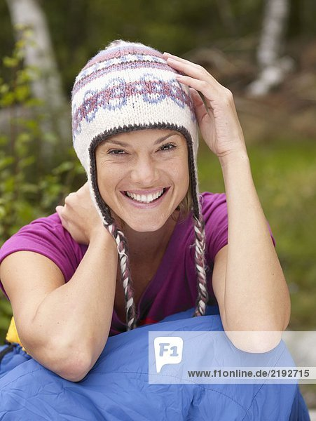 Woman sitting with a sleeping bag around waist smiling .