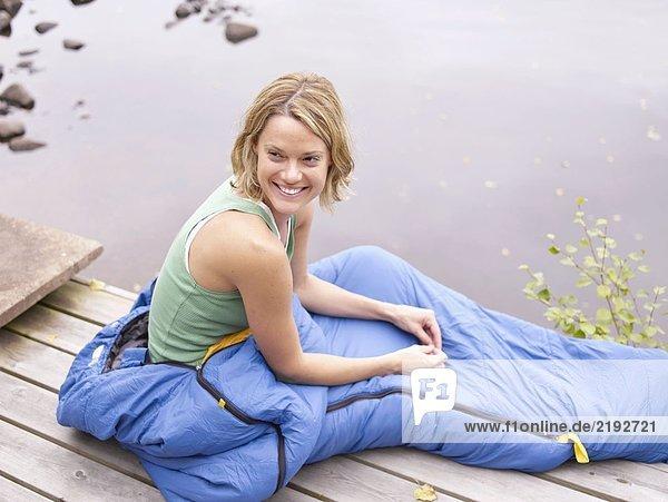 Frau mit Schlafsack um die Taille sitzend auf dem Dock lächelnd.