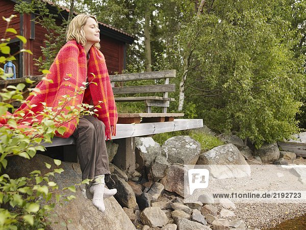 Woman with blanket wrapped around her sitting on dock smiling.