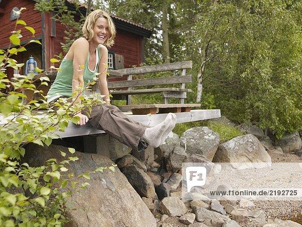 Woman sitting on dock smiling.