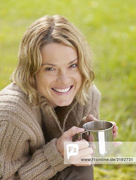 Woman holding mug outdoors smiling.
