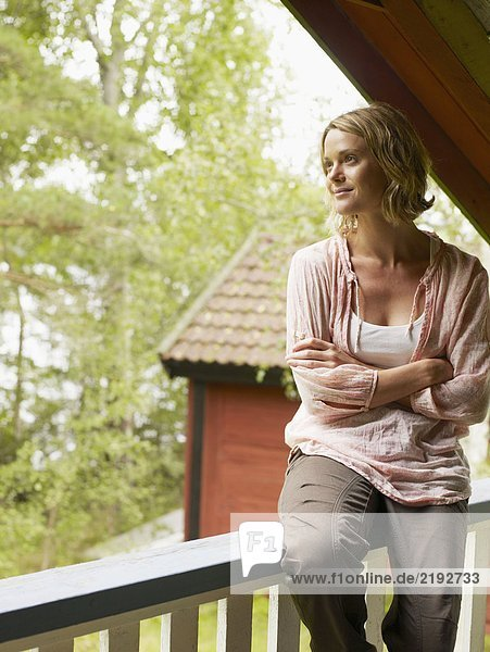 Woman on upstairs balcony with arms crossed smiling.