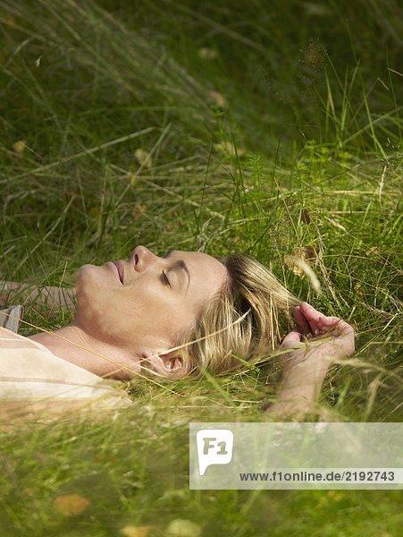 Woman lying in the grass sleeping.