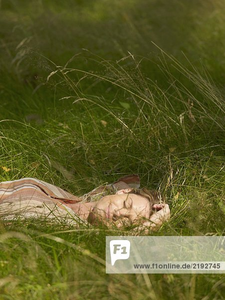 Woman lying in the grass with eyes closed smiling.