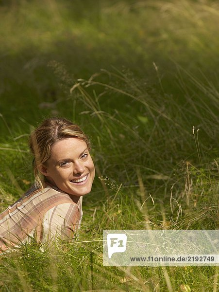 Woman lying in the grass smiling.
