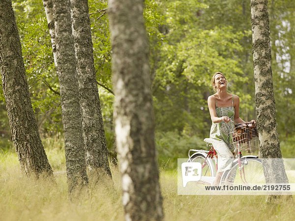 Woman riding a bike in forest smiling.
