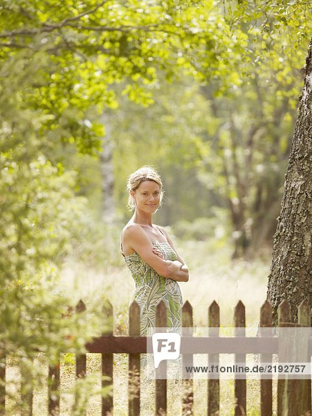 Woman standing by wooden fence smiling.