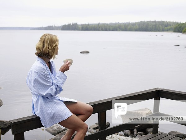 Woman sitting on a porch by the water holding a mug.
