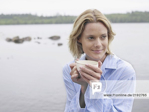 Woman by the water holding a mug.