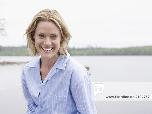 Woman laughing outdoors by the water.