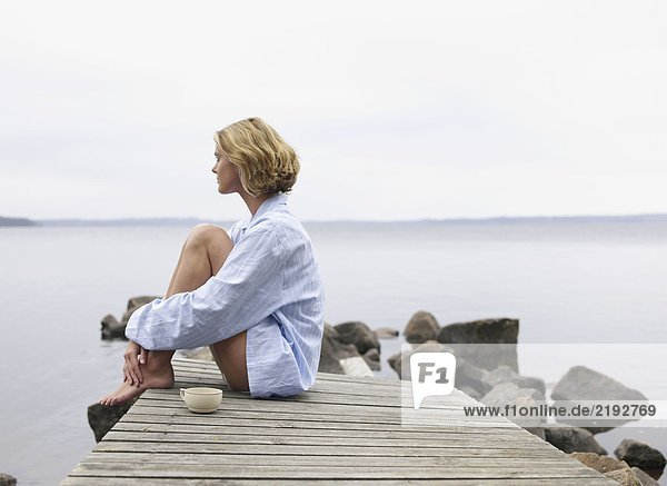 Woman with eyes closed sitting on a dock with a mug.