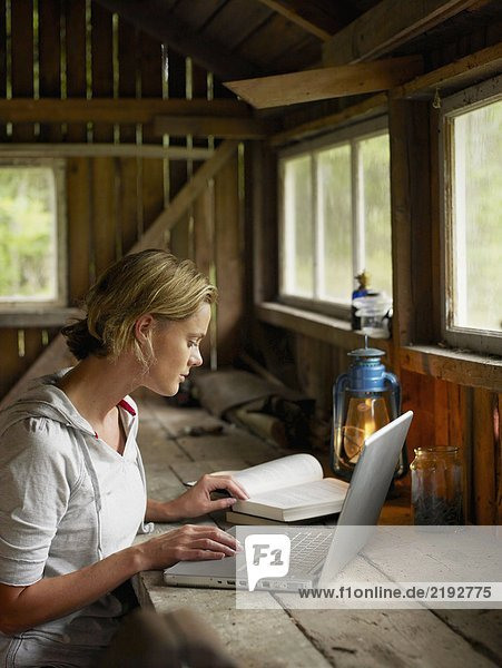Woman with laptop and book sitting at table in cabin.