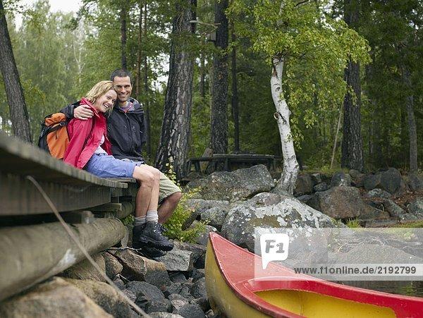 Ein Paar sitzt auf einem Dock in der Nähe eines Bootes und lacht.