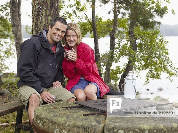 Couple sitting in a park by a fire pit smiling.