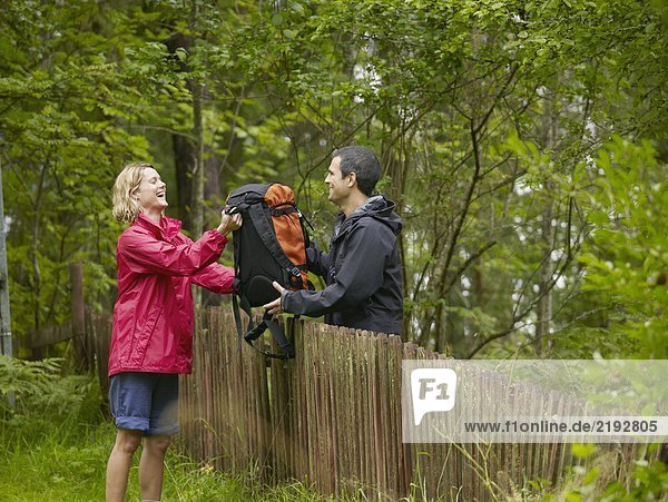 Man handing laughing woman backpack over a fence.