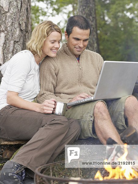 Couple by a fire pit with a laptop smiling.