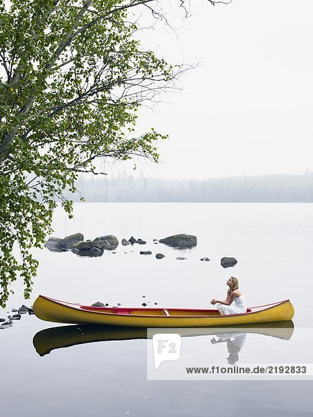 Woman sitting in a boat looking up.