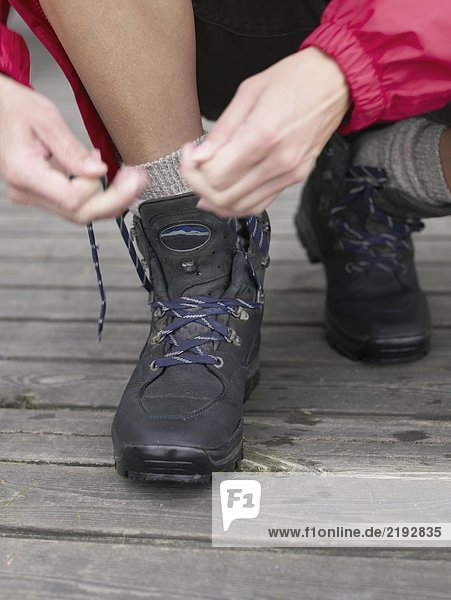 Woman's shoes being laced up.