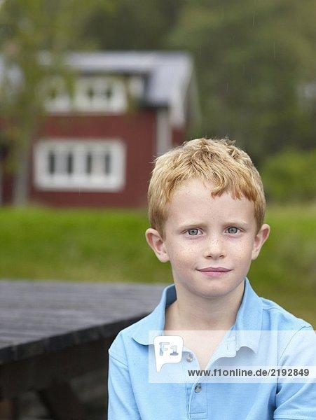 Kleiner Junge sitzt am Tisch im Freien mit Haus im Hintergrund.