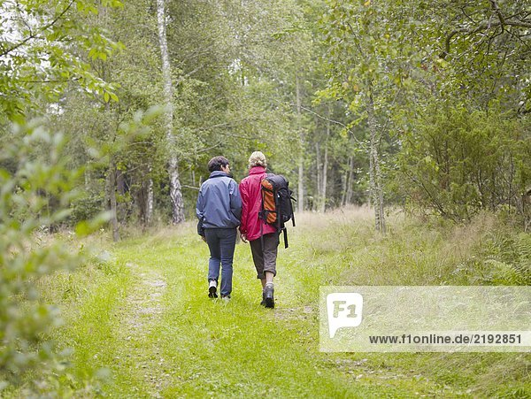 Two women walking through a forest with a backpack smiling.