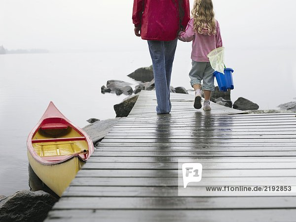 Woman and young girl holding hands walking on a dock.