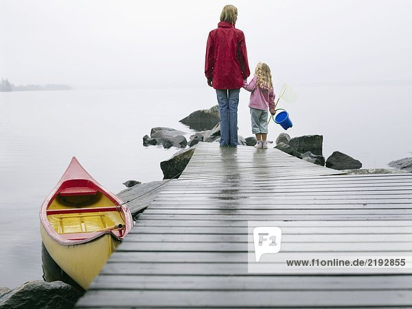 Woman and young girl holding a pail on a dock near a boat.