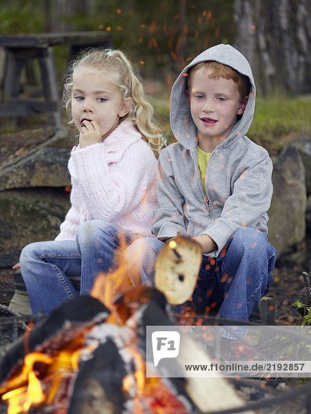 Young boy and young girl cooking toast over a fire at a campsite.