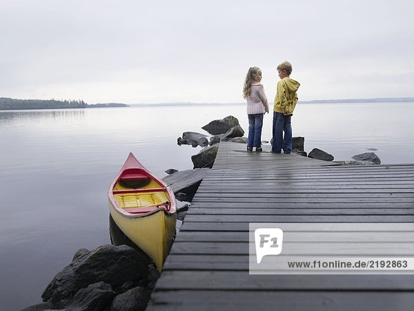 Young girl and young boy on a dock near a boat.