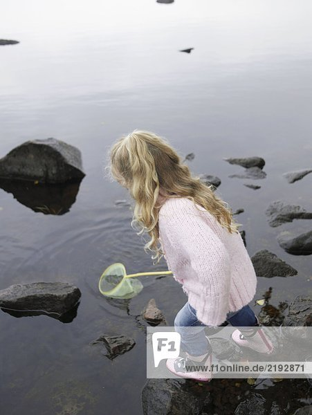 Young girl fishing in a lake with a net.