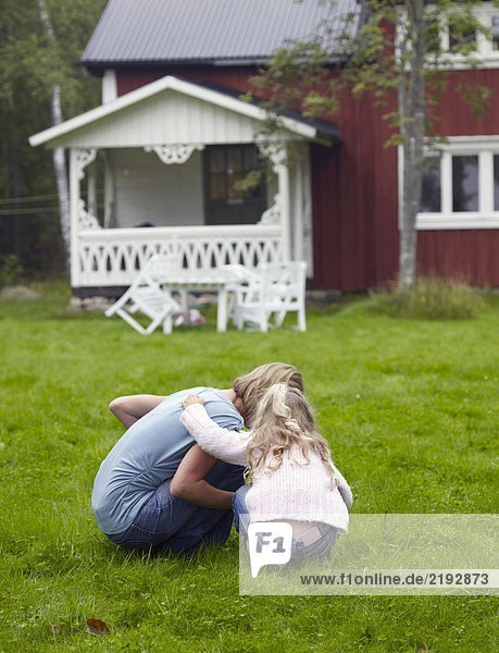 Woman with young girl crouched down in yard.