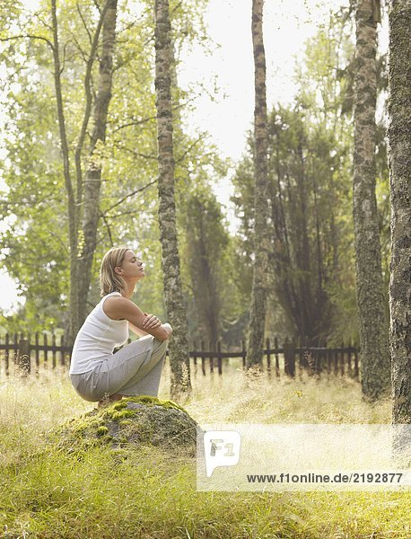Woman crouching on a large rock by a wooden fence.