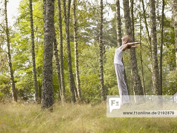 Woman standing on large rock in forest with arms outstretched.
