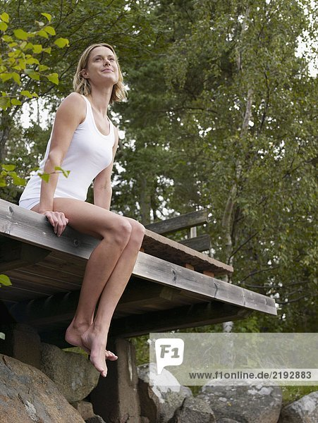 Woman sitting on dock with legs hanging over the side.