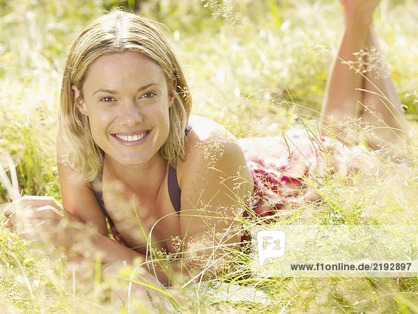 Woman lying in grass smiling.