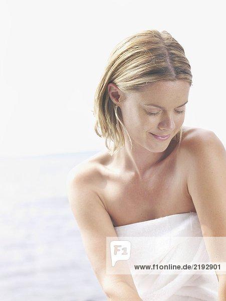 Woman wearing towel smiling.