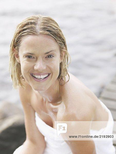 Woman wearing towel sitting on dock smiling.