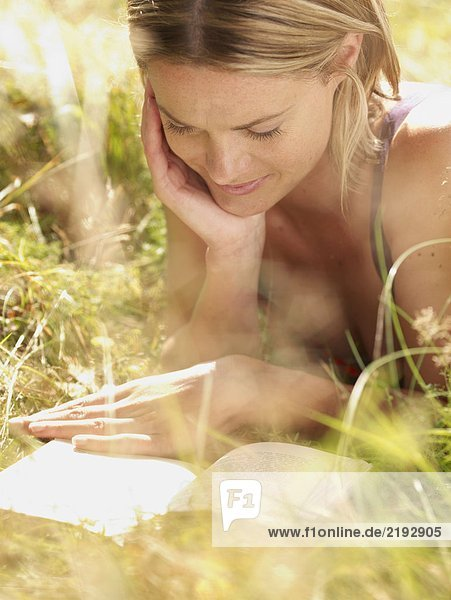 Woman lying in grass reading a book and smiling.