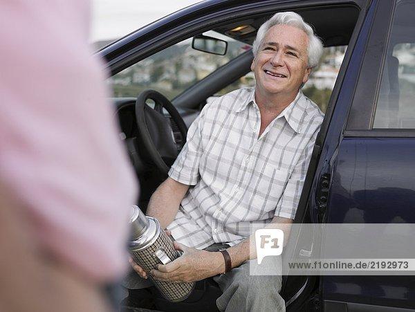 Älterer Mann sitzt im Beifahrersitz eines geparkten Autos  hält Flasche  lächelt