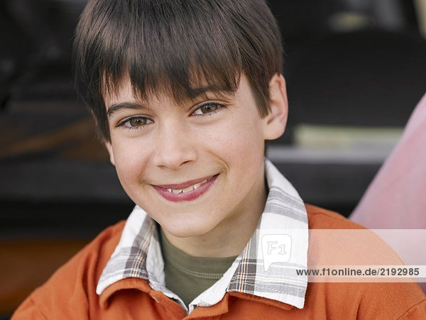 Boy (8-10) with brown eyes and hair  smiling  close-up  portrait