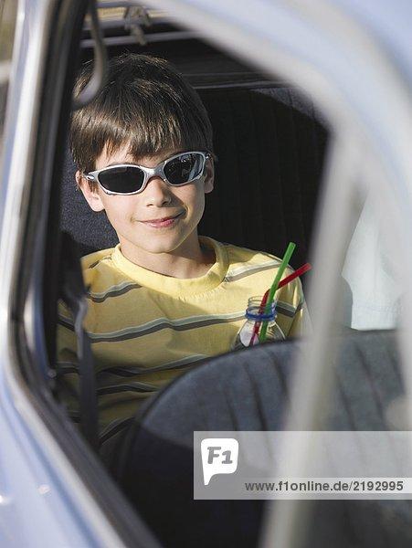 Junge (8-10) in Sonnenbrille sitzend auf dem Rücksitz des Autos mit Getränk  lächelnd  Portrait