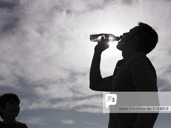Mann trinkt Wasser aus der Flasche  Sohn (8-10) schaut auf (hinterleuchtet  Streulicht)