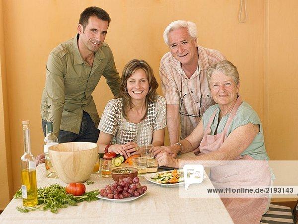 Seniorenpaar bei der Zubereitung des Essens zu Hause mit erwachsenen Nachkommen  lächelnd  Portrait