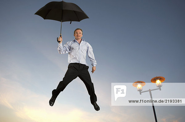 Geschäftsmann schwebend mit Regenschirm Geschäftsmann schwebend mit Regenschirm
