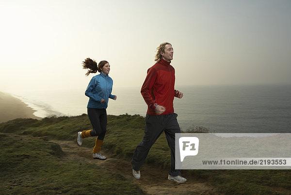 Ein junges Paar  das auf einem Pfad joggt.