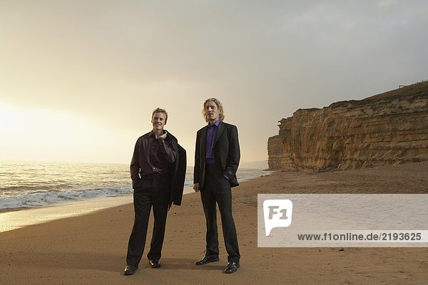 Zwei Männer stehen bei Sonnenuntergang am Strand.