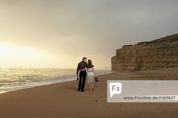 Ein Paar geht zusammen am Strand spazieren.