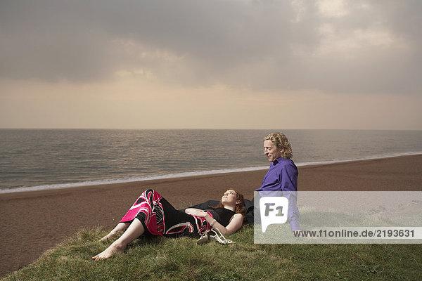Couple sitting next to a beach.