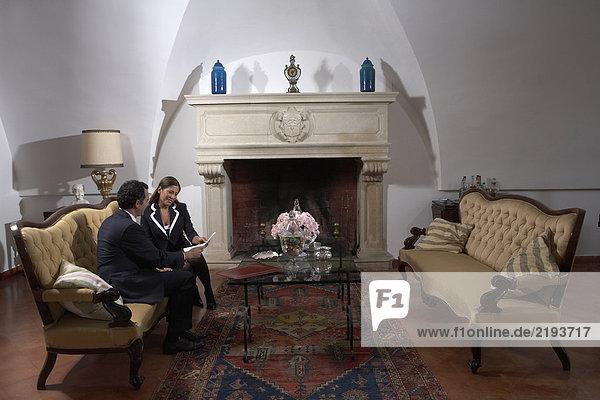 Reife Paare beim Lesen von Dokumenten im Wohnzimmer
