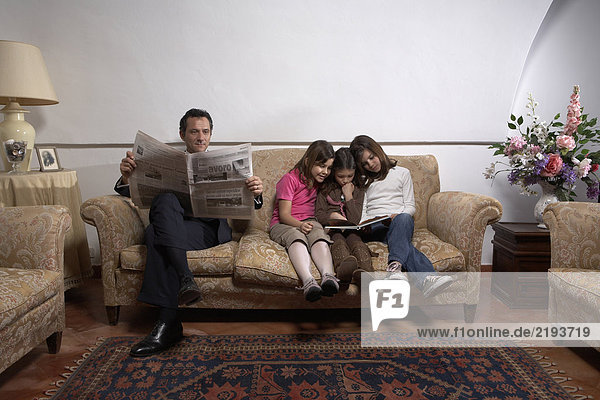 Man reading newspaper on sofa with three daughters (5-11)